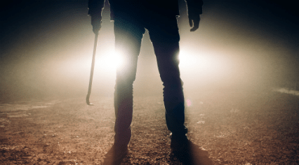 A man with a crowbar standing in front of the headlights of his vehicle at night.