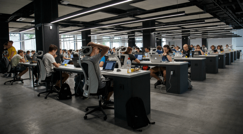A large office full of people working in at desks on computers